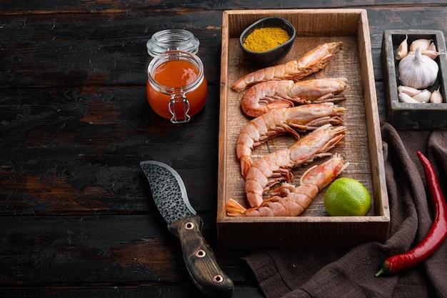 生のキングエビの大きな生の殻セット、木製の箱、古い暗い木製のテーブル
