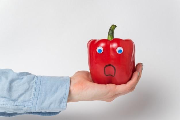 Большой красный болгарский перец, глазки на ладони. испуганный перец. белый
