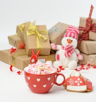 Large red ceramic cup with cocoa and marshmallows, behind a gift box and a christmas garland