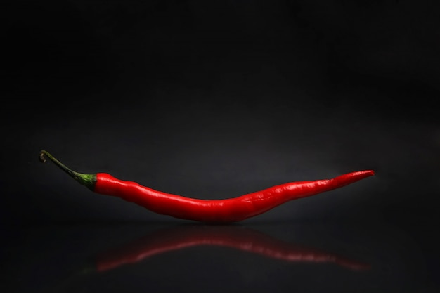 A large red chili isolated from a black background