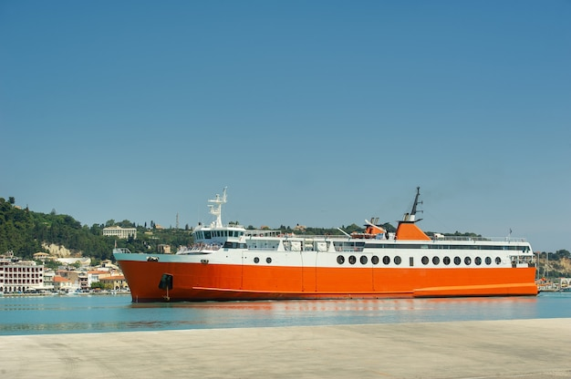 Large red ferry for transporting cargo and people in the mediterranean sea near the greek island
