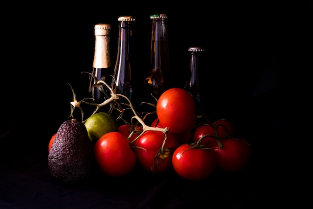 Large red and ripe tomatoes with lime avocado and bottle of beer on black background