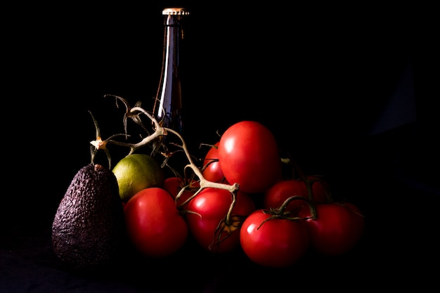 Large red and ripe tomatoes with lime avocado and bottle of beer on black