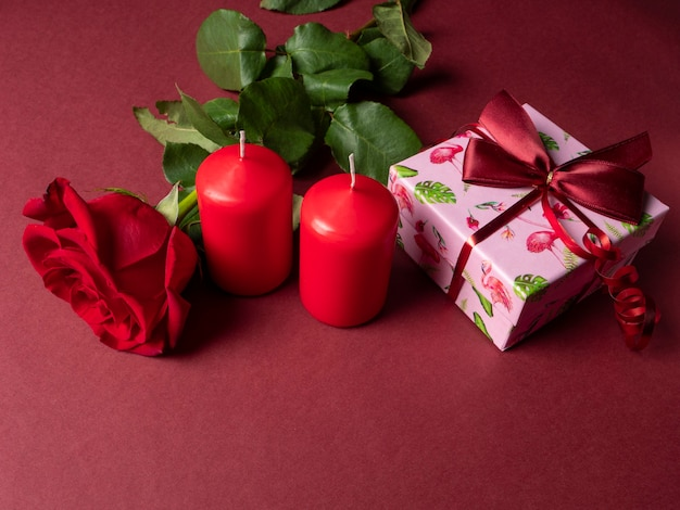 A large red rose that is next to two red large candles and a pink gift
