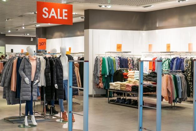 Большой красный знак с надписью sale в большом бутик-магазине одежды. большая распродажа одежды в большом современном торговом центре, тц