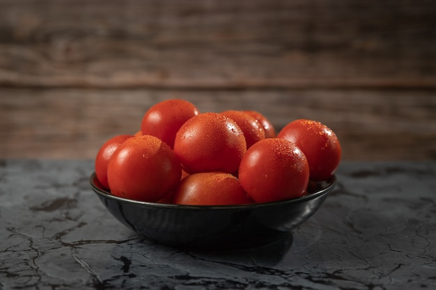 Large red tomatoes on a black plate, on a granite table