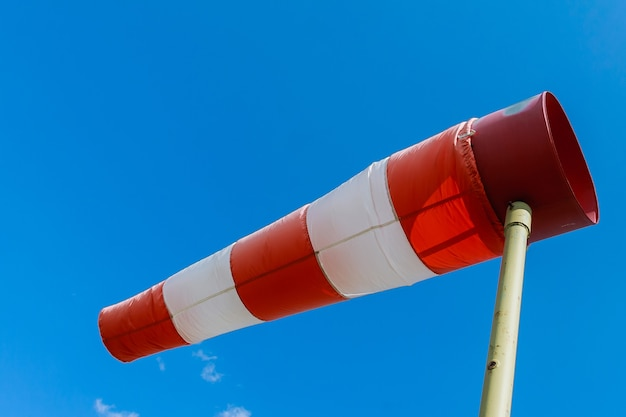 A large red white striped windsock against blue sky