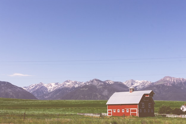 Large red wooden barn in a green field with rocky mountains