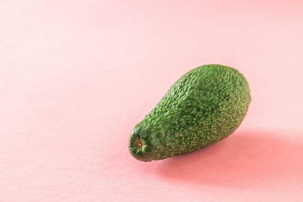 분홍색 배경에 큰 익은 아름다운 녹색 아보카도. 맛있는 열대 야채.
