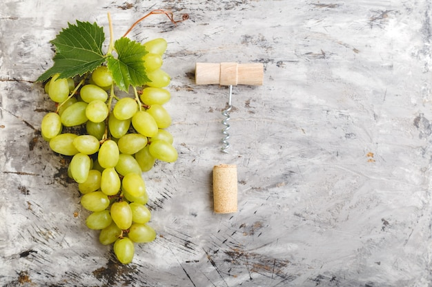 Large ripe green riesling grape grone corkscrew and wine cork stopper. ripe juicy green grapes on light gray concrete background top view copy space.