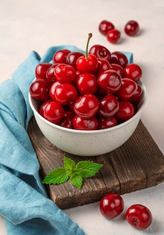 분홍색 배경에 베이지색 그릇에 큰 익은 빨간 체리. 여름 과일. 세로 보기입니다.