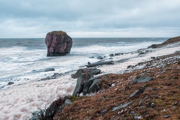Из моря выступает большая скала. волны с белой пеной катятся по каменистому берегу. терский берег, мыс корабельный на кольский полуостров.