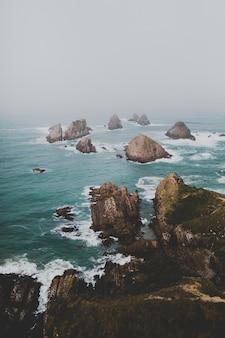 ナゲットポイントアフリリの大きな岩、霧の背景を持つニュージーランド