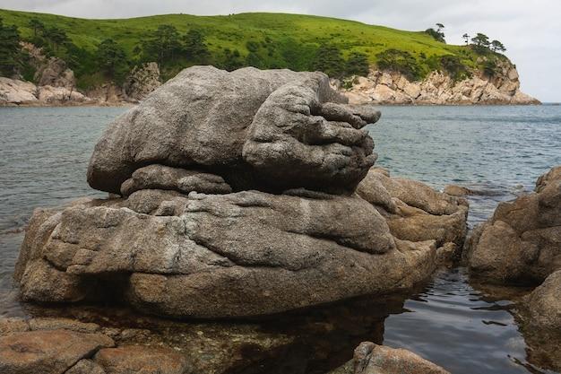 Большие скалы на пляже, летний морской пейзаж.