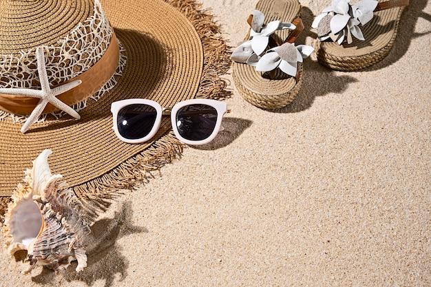 大きな丸い夏のわらの熱、サンダル、白いサングラス、素敵なビーチの砂の貝殻、上面図、コピースペース