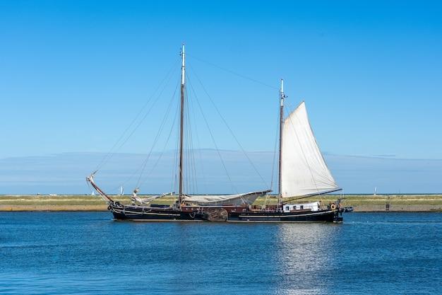Grande barca a vela con vele bianche che navigano sulla superficie dell'acqua sotto un cielo azzurro chiaro