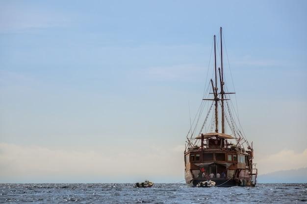 スキューバダイバーが海に停泊している大型帆船。ひもにつないで2つの膨脹可能なモーターボート