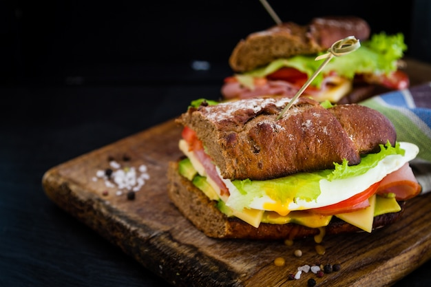 Large sandwich with avocado ham chese and egg