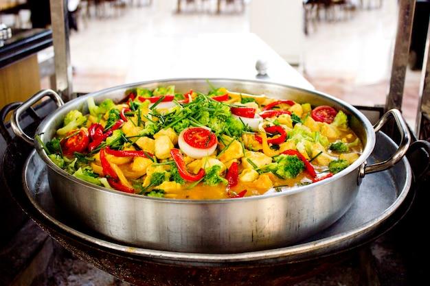 Large saucepan of stewed vegetables on fire