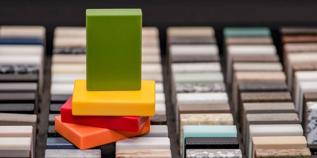 カウンタートップや床用の石のサンプルの豊富な品揃え。サンプルボックス内の人工アクリル石の断片。さまざまなテクスチャのカウンタートップの色合いのセット