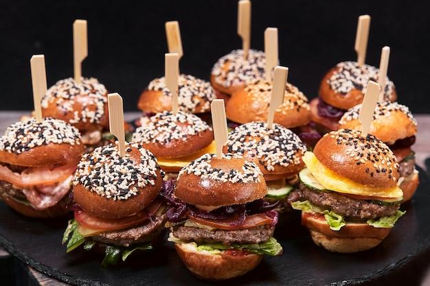 많은 햄버거, 치즈버거가 어두운 배경의 탁자 위에 놓여 있습니다. 세스 패스트푸드. 어두운 배경, 복사 공간.
