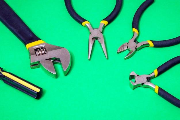 Большой набор инструментов для мастера-сантехника или электрика на зеленом изолированном фоне