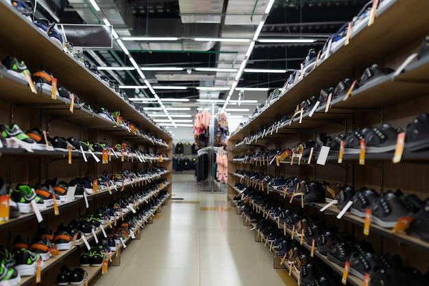 Большой обувной магазин с длинными полками, заполненными обувью