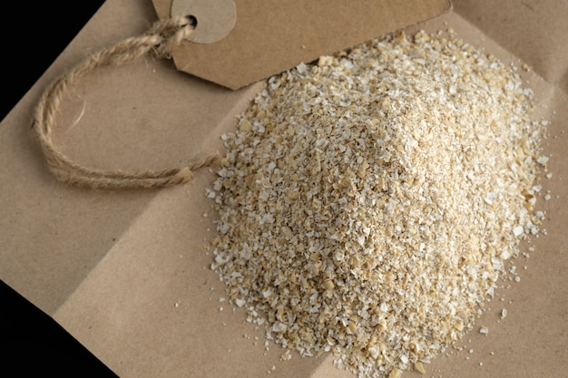 Large size oat bran, useful, cleansing, for a healthy diet on a black background