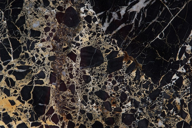 A large slab of dark expensive marble with yellow streaks, called new portoro.