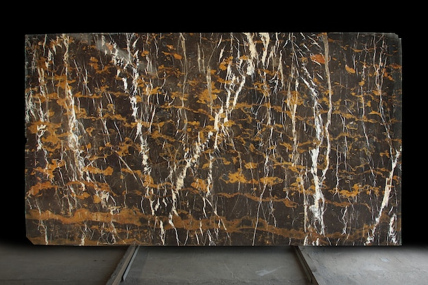 A large slab of polished natural stone. brown marble with yellow and white stripes called black and gold.