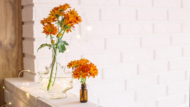 Large and small bouquets of orange chrysanthemums in vases