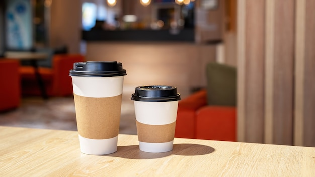 Large and small cup of coffee on a wooden table in a cafe. recycling idea