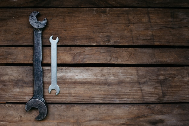 Large and small, old and new, two wrenches on wooden background, copy space