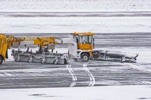 Большая снегоуборочная машина за работой на дороге во время снежной бури зимой.