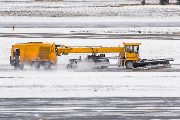 Large snow plowing machine at work on the road during a snow storm in winter.