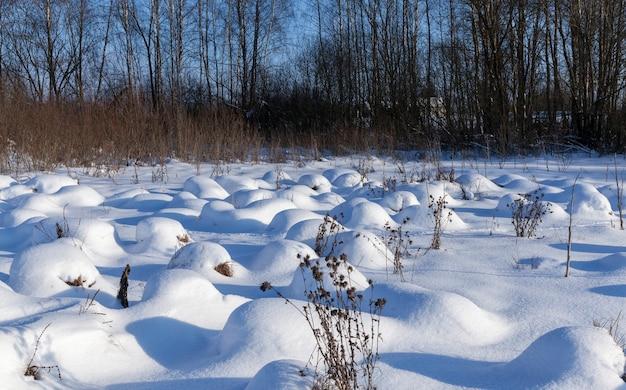 Большие сугробы после снегопадов и метелей, зимнего сезона с холодами и большим количеством осадков в виде снега