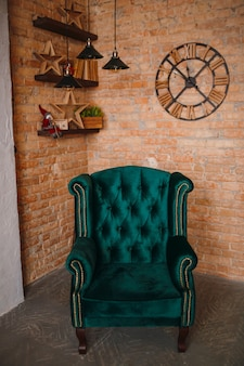 Large soft green armchair stands before a brick wall