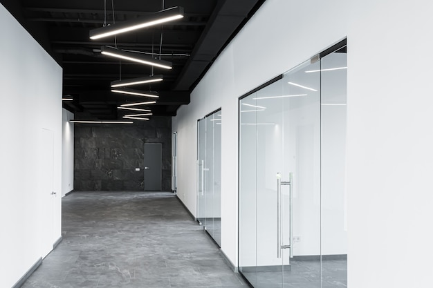 탁 트인 창문과 가구가없는 유리문이있는 넓은 사무실 센터