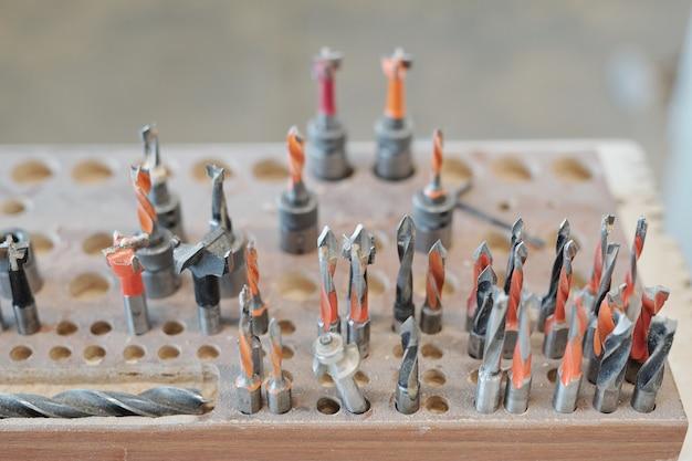 Большой квадратный инструментальный щиток с металлическим ключом, группа деталей для круглопильного станка и стопка длинных узких деревянных досок в мастерской