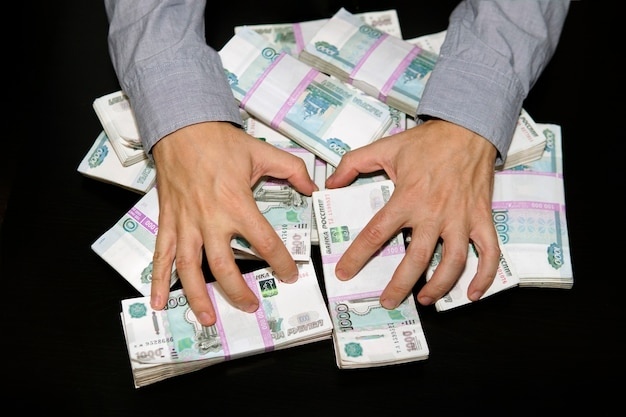 Large stack of banknotes, russian rubles, banknotes 1000 rubles. hands are grabbing money. lust for money.