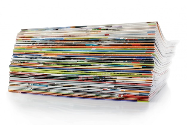 A large stack of magazines. on a white wall with shadow.