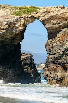 スペイン、ガリシアの大聖堂の有名なビーチにある海岸沿いの大きな石造りのアーチ。ルーゴ。