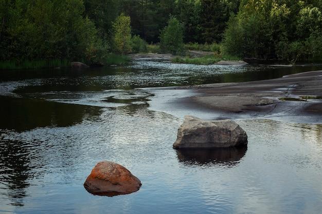 森の湖にある大きな石。水中の雲と空の反射。壮大な風景。