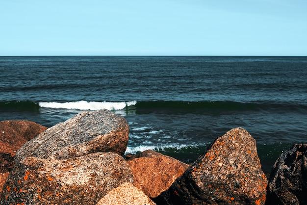 大きな石が波の前のビーチにあります。