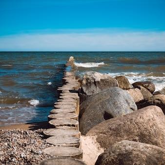 波の前のビーチには大きな石が横たわっています。