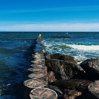 Большие камни лежат на пляже перед волнами.