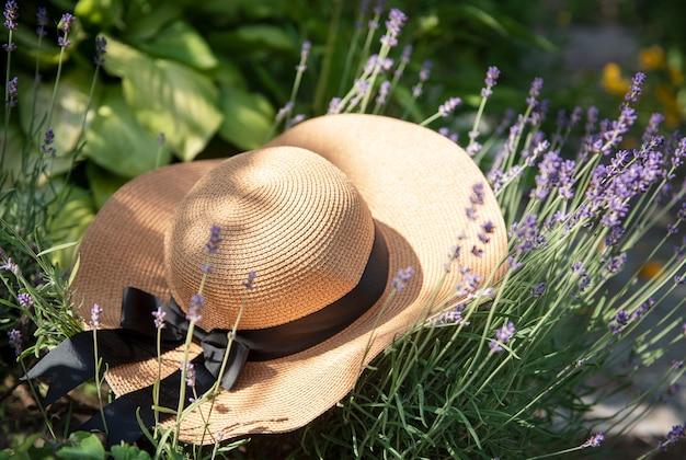 ラベンダーの茂みにある大きな麦わら帽子。ロマンチックな夏のコンセプト。