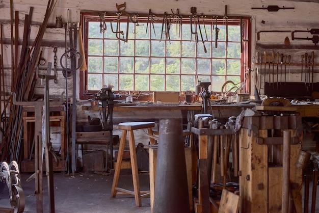 Большой стол у окна. старинная мастерская кузнеца с тисками челюсти и другими инструментами.