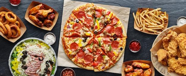 피자, 감자 튀김, 양파 링, 프라이드 치킨 및 닭 날개와 같은 음식을 꺼내는 큰 테이블