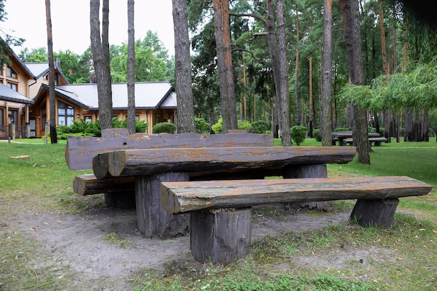 A large table and two benches of rough-hewn logs in a summer park. wooden houses in the background